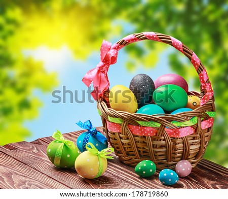 colored eggs in the basket on the table against the background of the garden