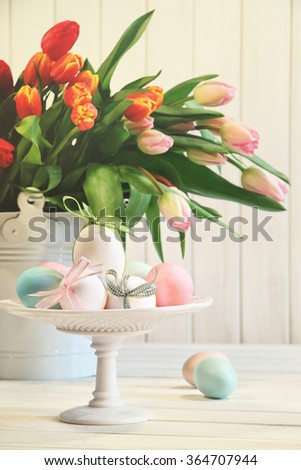 Colored eggs with bows with tulips in background - stock photo