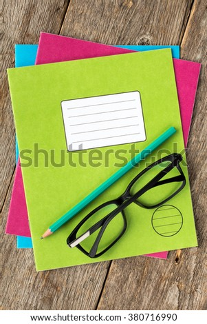 Colored exercise books,pencil and glasses on the wooden background