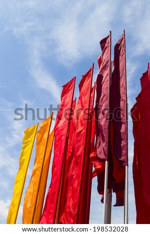 colored flags on blue sky background - stock photo