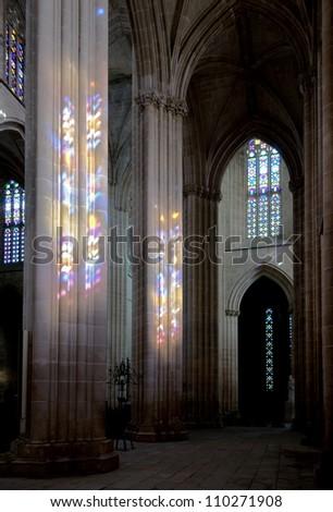 Colored flecks of sunlight from windows on the columns of Batalha Santa Maria da Vitoria Dominican abbey, Portugal - stock photo
