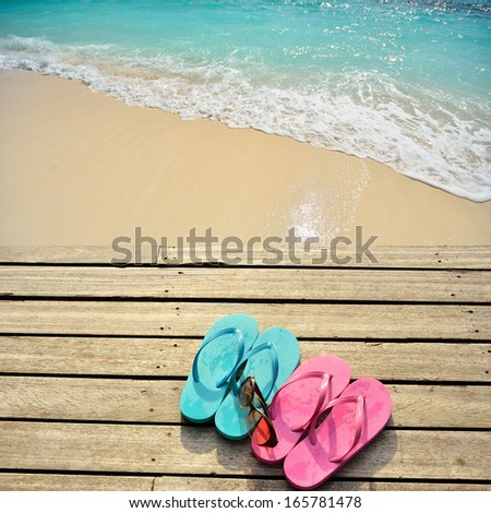Colored flip flops and sunglasses on the wooden platform beside sea  - stock photo