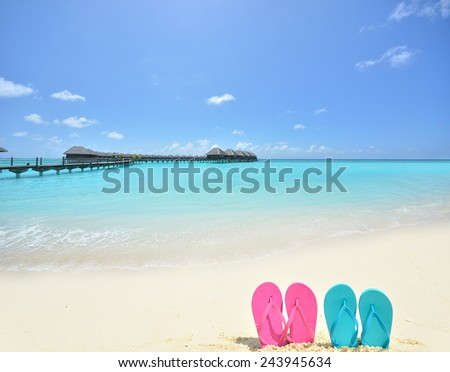 Colored flip flops on the tropical beach -- Tropical honeymoon vacation concept - stock photo