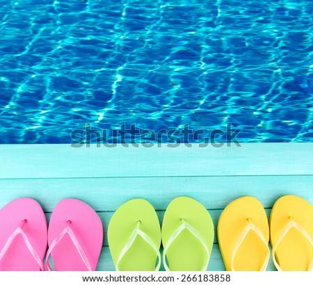 Colored flip flops on wooden platform beside sea - stock photo