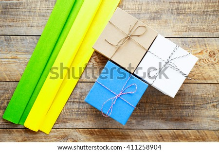 Colored gift boxes on wooden background with ribbon - stock photo