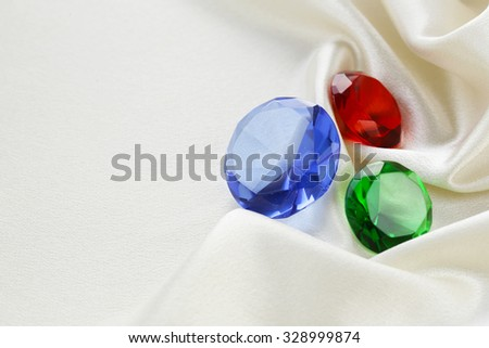 colored glass diamonds on a soft silk background - stock photo
