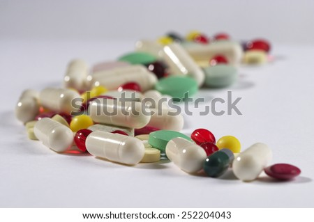 Colored glossy rounded multi vitamin pills macro shot over white background