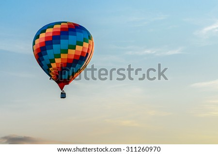 Colored hot air balloon flying in the blue sky - stock photo