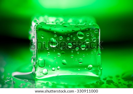 Colored ice cubes on wet glass table. Selective focus. Shallow depth of field. Toned. - stock photo