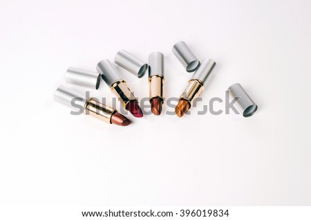colored lipsticks on a white background with open caps