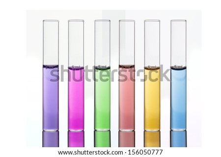 Colored Liquids in Six Test Tubes with Reflection on a White Background