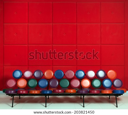 Colored metal bench in the lobby on a background of soft red walls - stock photo