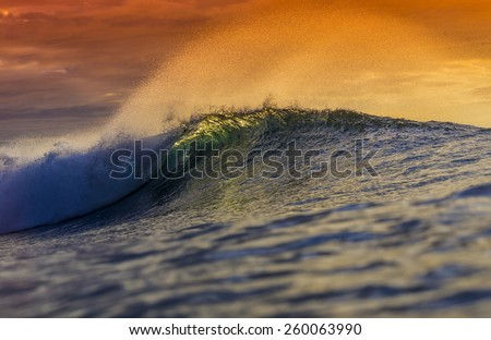 Colored Ocean Wave Falling Down at Sunset Time.