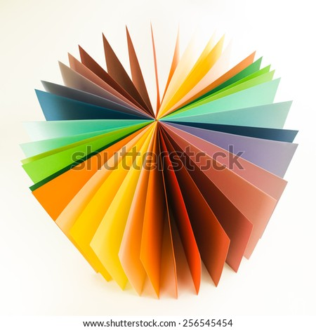 colored origami paper arranged in circle fan shape on white background - stock photo