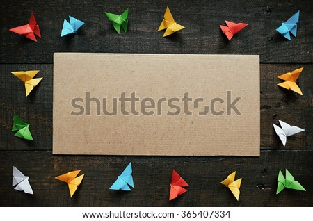 Colored origami paper butterflies frame on dark brown aged wood background. Valentines day horizontal postcard template. Cardboard space for copy, text, lettering. - stock photo