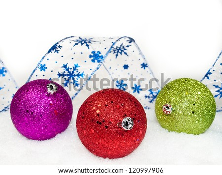 colored ornaments and ribbon in the snow