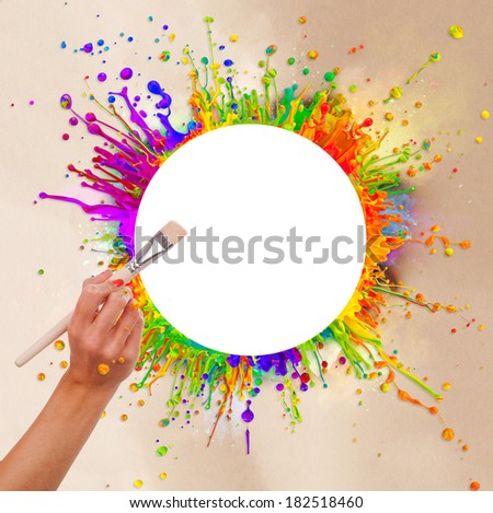 Colored paint splashes in round shape with free space for text in center. Woman hand holding paintbrush. Paper texture around - stock photo