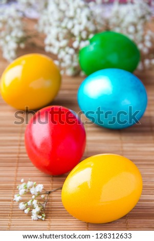 Colored painted eggs on bamboo table