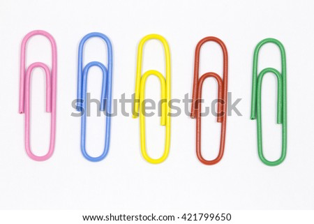 colored paper clips on a white background - stock photo