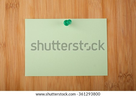 Colored paper note on wooden background. Copy space.