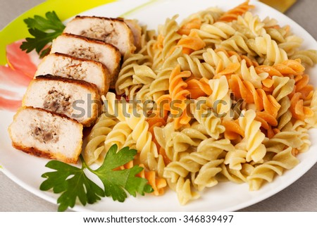 Colored pasta on a plate with parsley and chicken roll