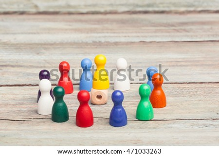 colored pawns, in a circle, one yellow pawn  on a die in the middle. working together conceptual on wood table, studioshot, grey background
