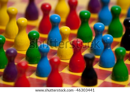 Colored pawns on play table - stock photo