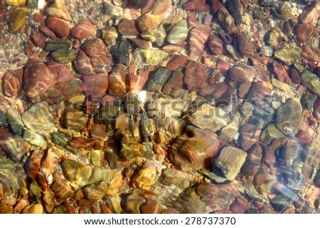 Colored pebbles on the beach with water texture background. - stock photo