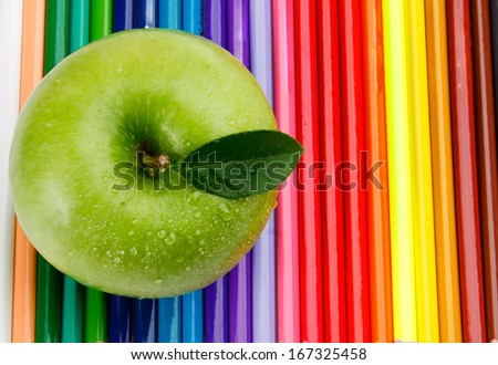 Colored pencils and a green apple - stock photo