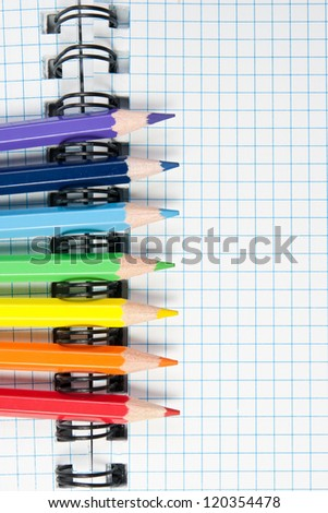 Colored pencils and a notebook background - stock photo