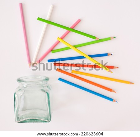 colored pencils and glass - stock photo