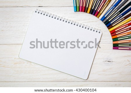 colored pencils and notepad on white boards, , flat lay