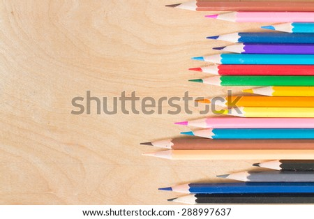 Colored pencils horizontal/Many different colored pencils on wood background