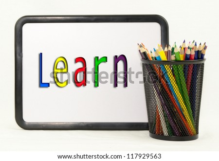 Colored pencils in a holder with the word  learn on a dry erase board