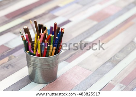 Colored pencils in a metal bucket. Different children's pens for painting on wooden background.