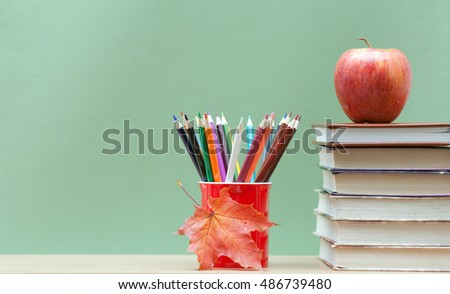Colored pencils in a mug, the books and an apple