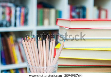 Colored pencils in glass pen holder with pile of books out of focus in background