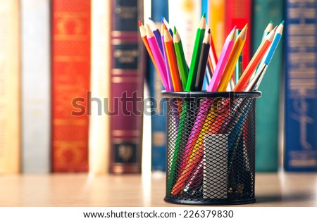 Colored pencils in pencil case on the bookshelf - stock photo