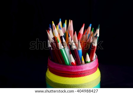 Colored Pencils in Rainbow-Colored Jar on Dark Background