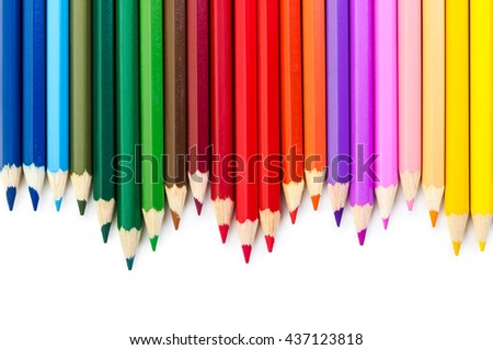 Colored pencils lined in row, isolated on white background. Top view.