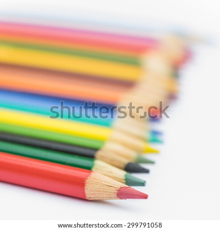 Colored pencils lined up on white background - stock photo