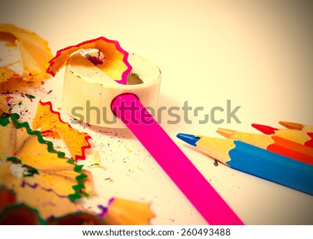 colored pencils, sharpener and shavings on white background with copy space. instagram image retro style - stock photo