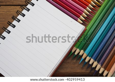 Colored pencils with notebook on wood background