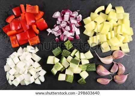 Colored peppers and onions diced on a black board. - stock photo