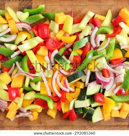 Colored peppers and onions diced on a chopping board - stock photo