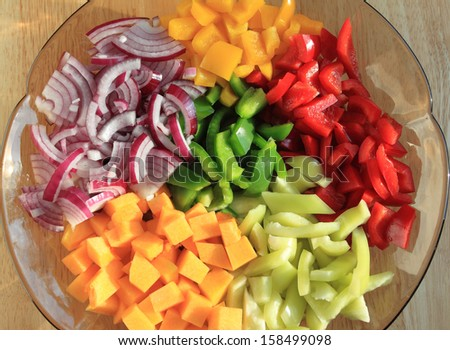 Colored peppers and onions diced on a plate. - stock photo