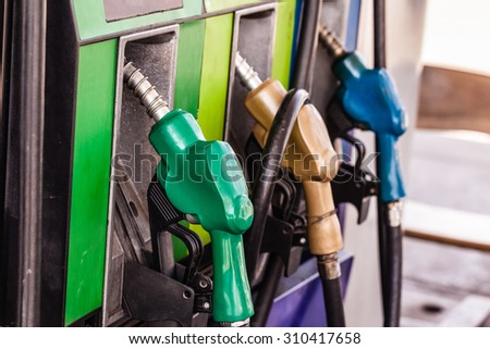 colored petrol gas pump nozzles in a service station - stock photo
