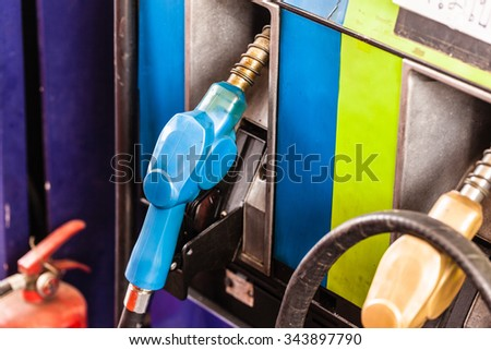 colored petrol gas pump nozzles in a service station