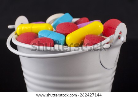 Colored pills medicine in a white bucket isolated on black background - stock photo
