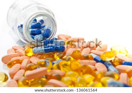 colored pills spill out of the box - stock photo